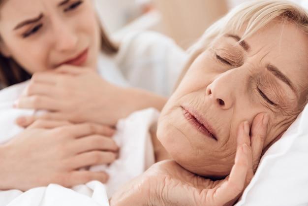 Close-up garota está cuidando da mulher idosa na cama em casa.