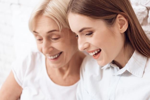 Close-up garota está cuidando de mulher idosa sorriem juntos