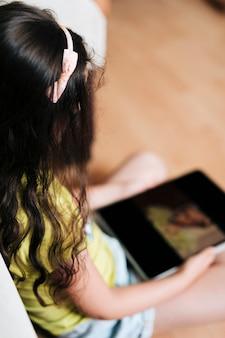 Close-up garota olhando seu tablet no chão