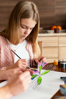 Close-up garota pintando borboleta