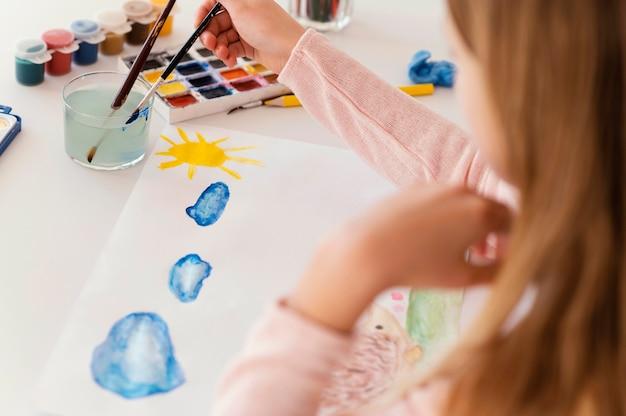Close-up garota pintando nuvens