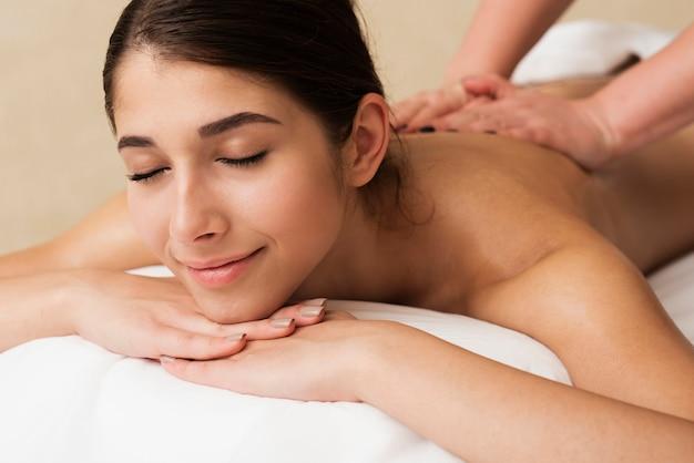 Close-up garota relaxada, recebendo uma massagem