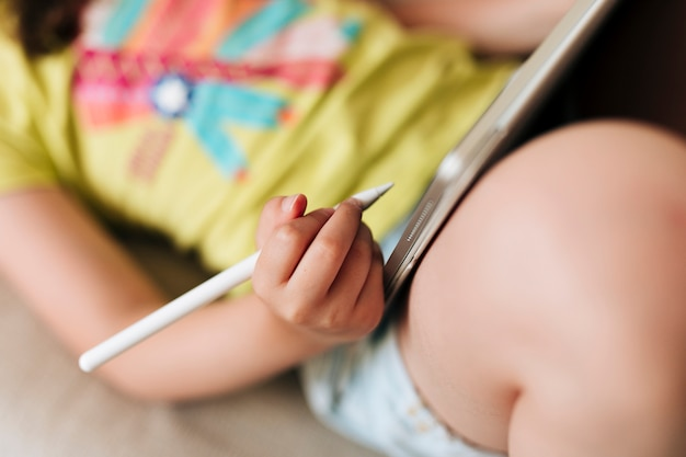 Close-up garota sentada no sofá com tablet e caneta