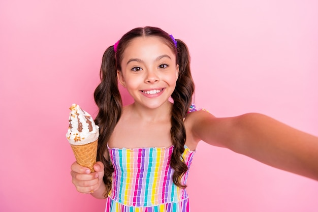 Close-up garotinha engraçada segurando grande cone de sorvete fazendo selfies