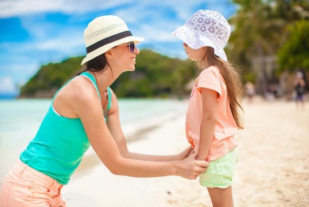 Close-up, garotinha está segurando sua jovem mãe na praia