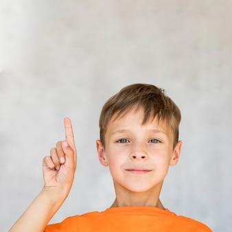 Close-up garotinho apontando para cima