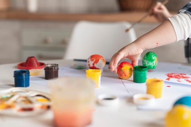 Close-up garotinho pintando ovos para a páscoa
