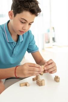 Close-up garoto brincando com pedaços de jenga