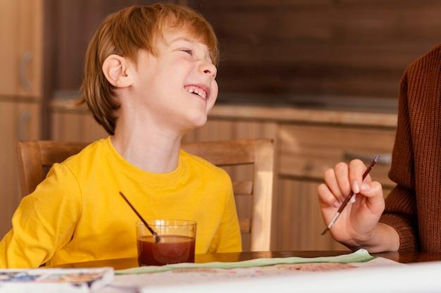 Close-up garoto feliz com itens de pintura