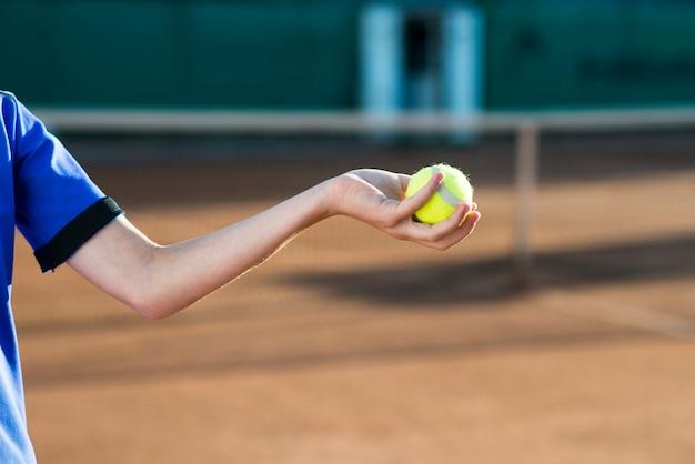 Close-up garoto segurando uma bola de tênis na mão