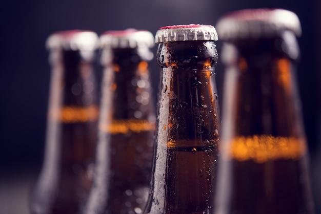 Close up garrafas de vidro de cerveja com gelo no fundo escuro