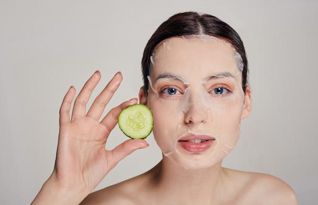 Close-up gentil sofisticada mulher calma em uma máscara hidratante com um pepino fresco no rosto sério com os olhos abertos e a mão direita segura um pepino perto do rosto