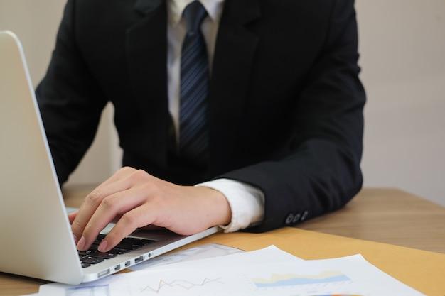 Close-up gerente de foco homem tipo de mão de trabalho no dispositivo de notebook
