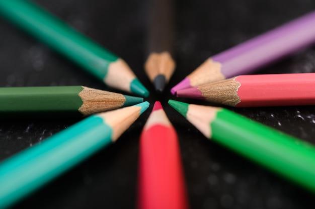 Close-up, giz de cera de madeira dispostos em uma roda de cores.
