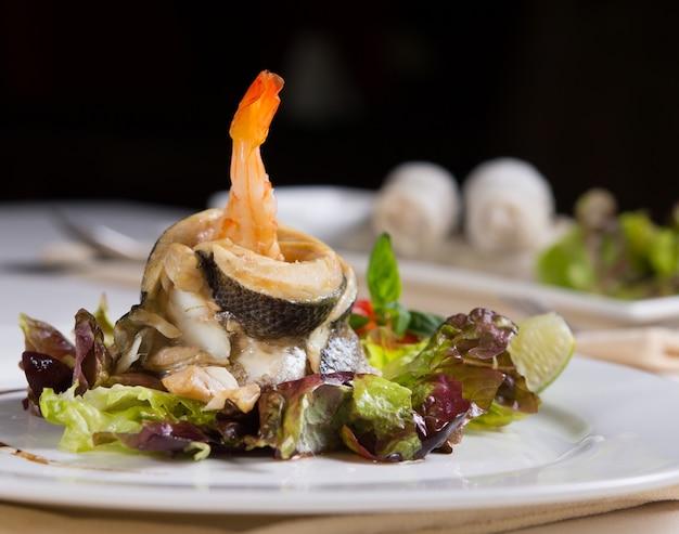 Close-up gourmet apetitosa receita de frutos do mar frescos em vegetais. servido na mesa do restaurante durante o jantar.