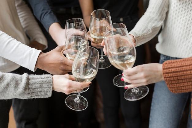 Close-up grupo de amigos brindando com taças de vinho