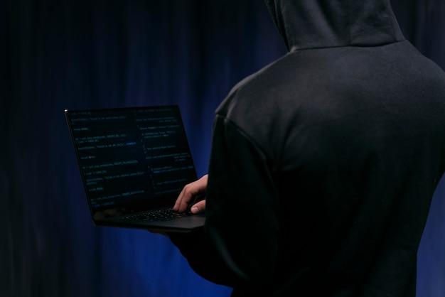 Close-up hacker segurando laptop