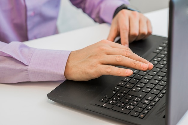 Close up hands homem multitarefa usando o laptop conectando internet, internet do conceito de coisas, layout do local de trabalho com mesa de madeira e laptops, espaço para cópia, espaço de trabalho confortável