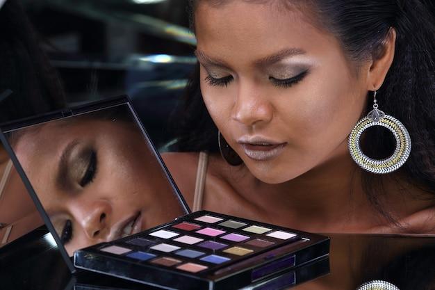 Close up head shot de 20 anos mulher asiática com moda maquiagem sobre espelho refletir seu rosto. garota de pele bronzeada olha para palete de cosméticos para maquiagem com ângulo de reflexão de fundo escuro