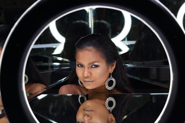 Close up head shot de 20 anos mulher asiática com moda maquiagem sobre espelho refletir seu rosto. menina de pele bronzeada expressa sentimento forte, sorriso, feliz com ângulo de reflexão de fundo escuro