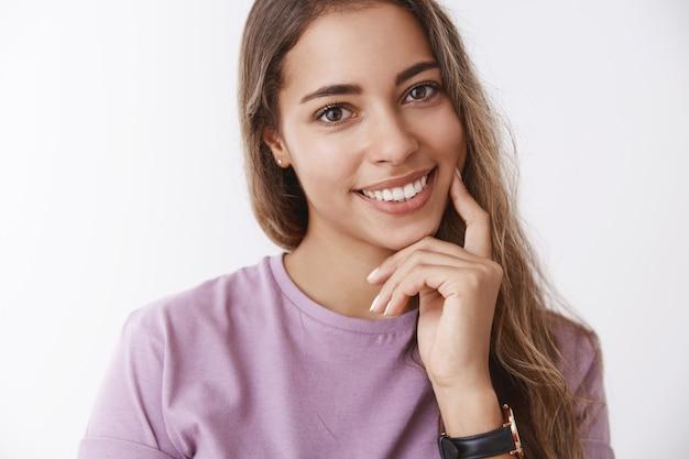 Close-up hispânico fofa terna mulher de 25 anos inclinando a cabeça sedutora sorrindo rindo alegremente, sentindo-se feliz, tocando o dedo da bochecha, cuidando da pele, lutando contra cicatrizes faciais, resultado de produtos para a pele deliciosos