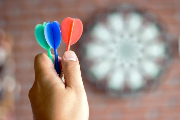 Close up hold hold three color arrow no jogo de dardo
