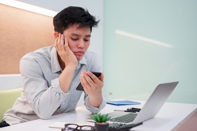 Close-up homem asiático sentindo entediado e sonolento ao jogar smartphone, conceito de estilo de vida as pessoas