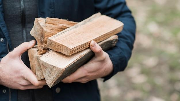Close-up homem carregando madeira