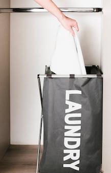 Close-up homem colocando as roupas no cesto de roupa suja