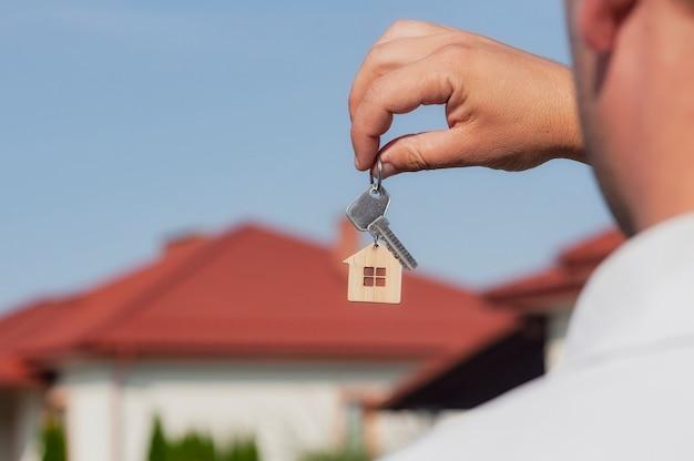 Close-up, homem com as chaves da casa nas mãos contra o pano de fundo de edifícios residenciais
