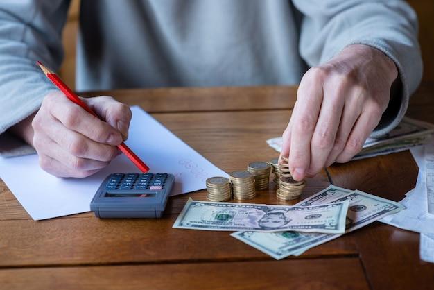 Close-up homem com calculadora contando, fazendo anotações em casa, mão é escreve em um caderno. moedas empilhadas arranjadas no deesk. conceito de finanças de poupança.