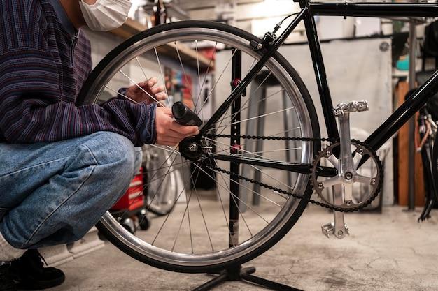 Close up homem com máscara lubrificando bicicleta
