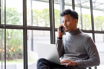 Close-up homem de negócios asiáticos falando de smartphone para trabalhar no escritório