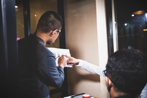 Close-up homem de negócios asiáticos presentes dados tocolleagues na reunião