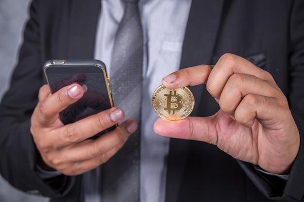 Close-up homem de negócios com bitcoin e usando telefone celular