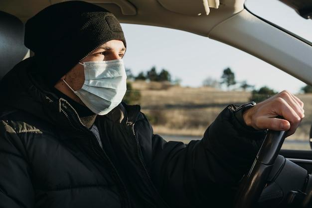 Close-up homem dirigindo com máscara de proteção