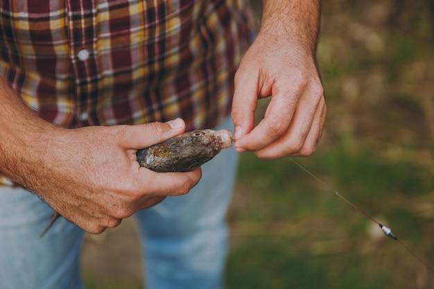 Close-up homem em jeans e camisa quadriculada remove peixes capturados com um anzol na vara de pescar em um fundo verde borrado. estilo de vida, recreação, conceito de lazer de pescador. copie o espaço para anúncio.
