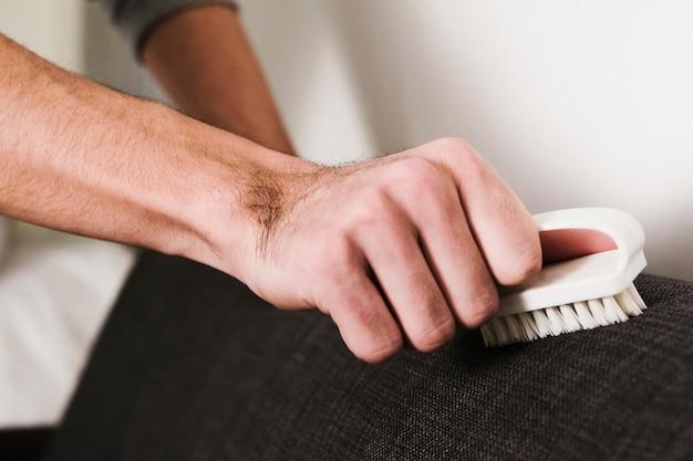 Close-up homem escovando o sofá