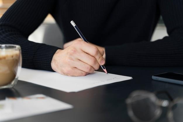Close-up homem escrevendo carta