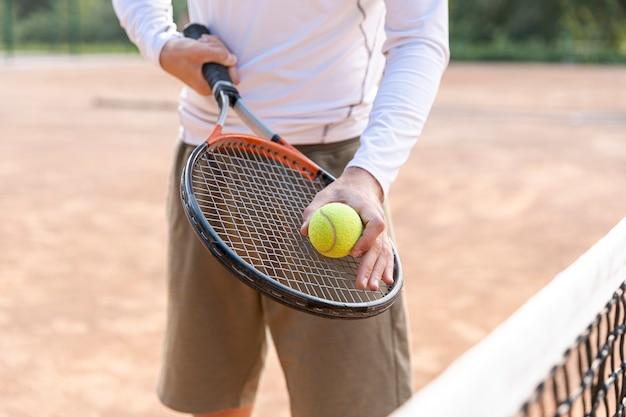 Close-up, homem, segurando, bola tênis, ligado, raquete