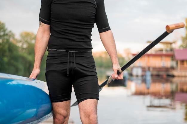 Close-up homem segurando canoa e remo