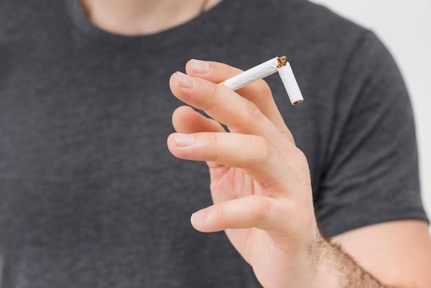 Close-up, homem, segurando, quebrada, cigarro, seu, dois, dedo