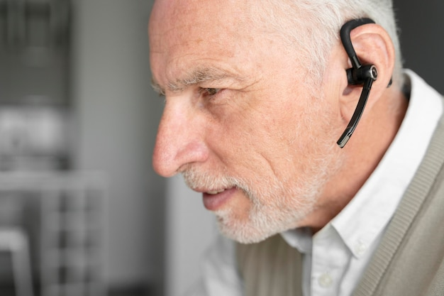 Close-up homem sênior usando fone de ouvido