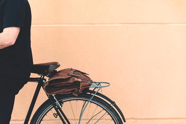 Close-up, homem, sentando, bicicleta, contra, bege, parede
