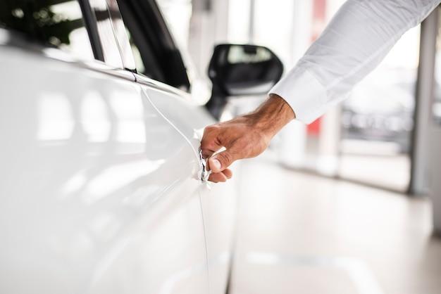 Close-up homem testando o carro na concessionária
