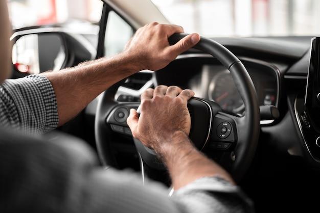 Close-up homem tomando carro para um test drive
