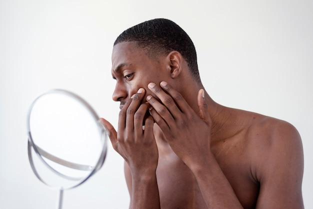 Close-up homem verificando o rosto dele