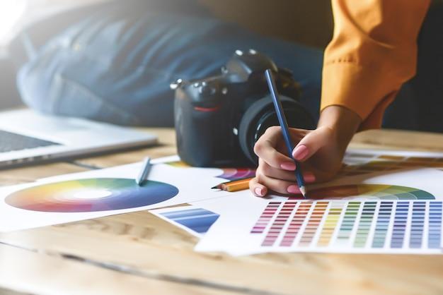 Close up hoto do trabalho em equipe de designers de interiores com plantas de construção de casas na mesa do escritório, arquitetos trabalhando com paleta de várias cores para escolher a melhor cor para o design.