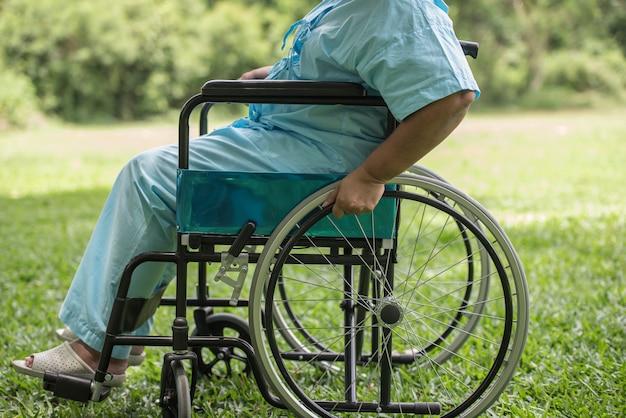 Close-up idosa solitária sentado na cadeira de rodas no jardim no hospital