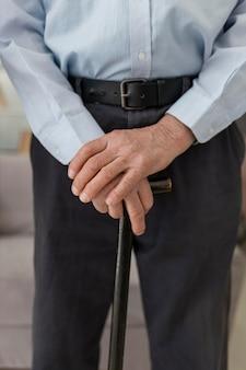 Close-up idoso segurando uma bengala